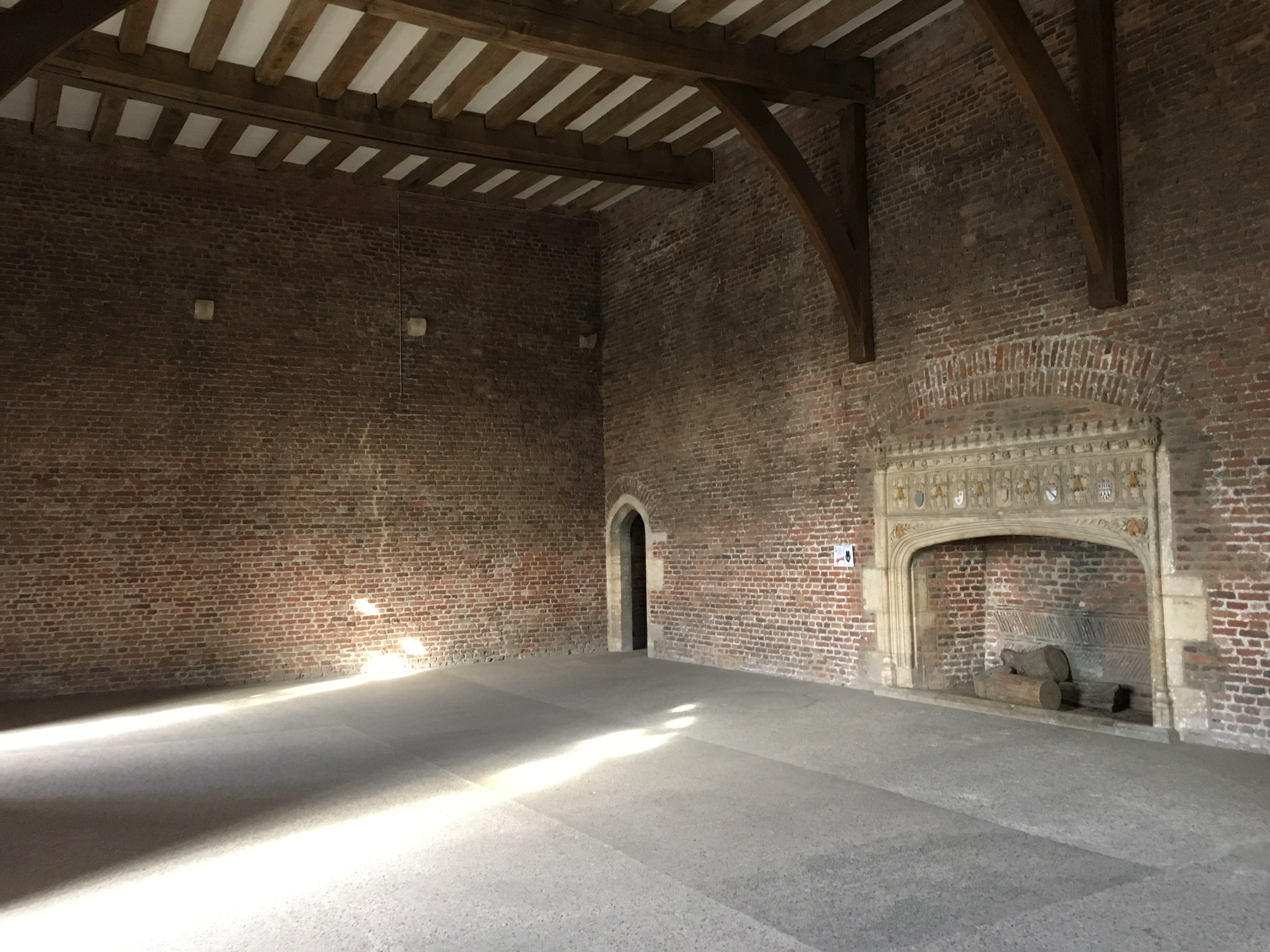 An internal room built of Tudor red-brick with a large central Tudor fireplace.