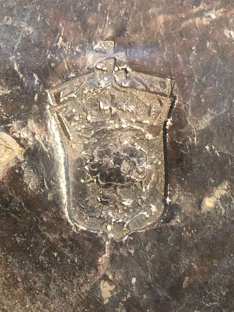 An ingot of lead with the stamp of a Tudor rose and crown above it.