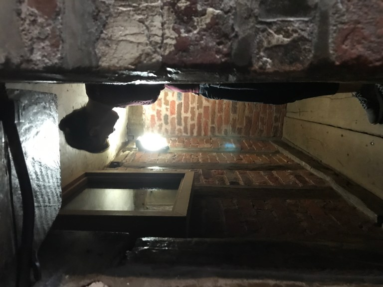 Woman inside one of the priest hides at Harvington Hall