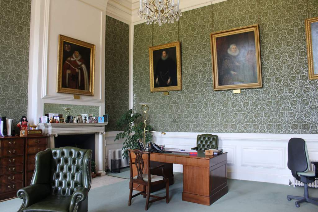 A room where Katherine of Aragon died at Kimbolton castle with chairs, a desk and portraits on the wall.