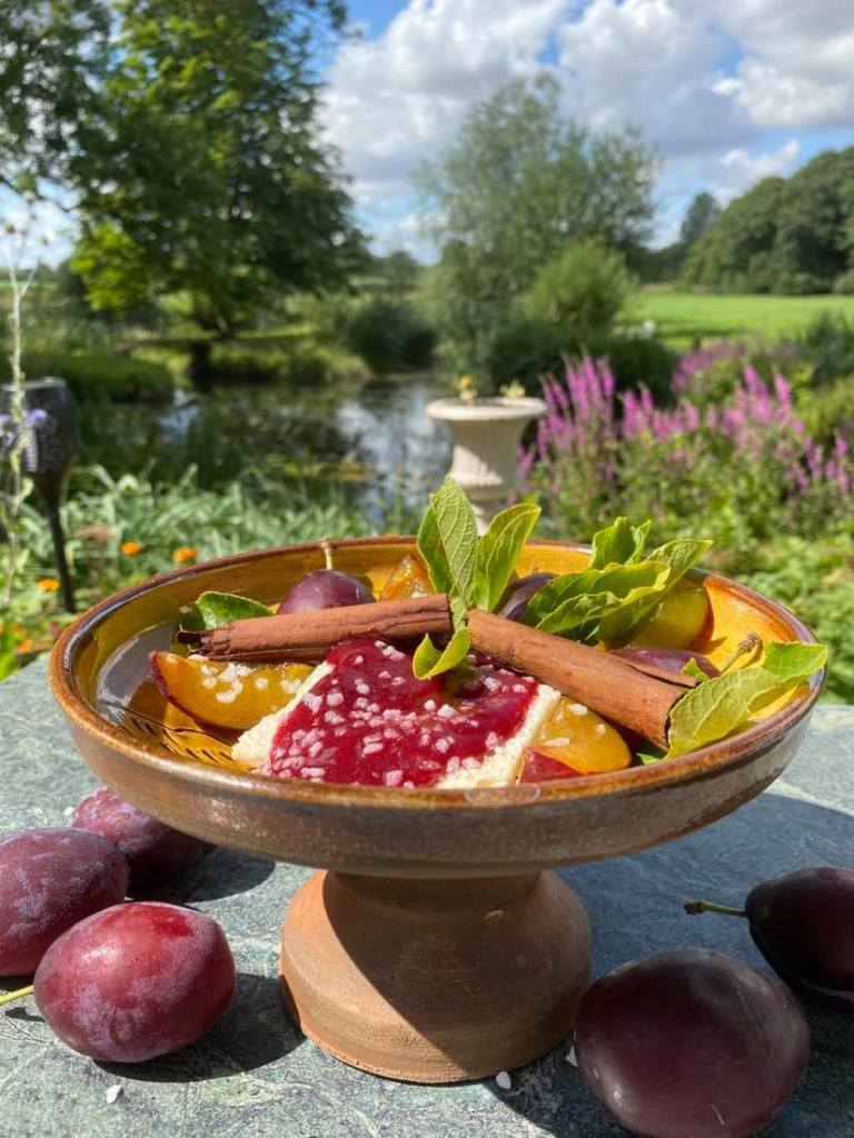 A picture of Tudor Plum Tart  on a pedestal platter in a garden with fresh plums around the base