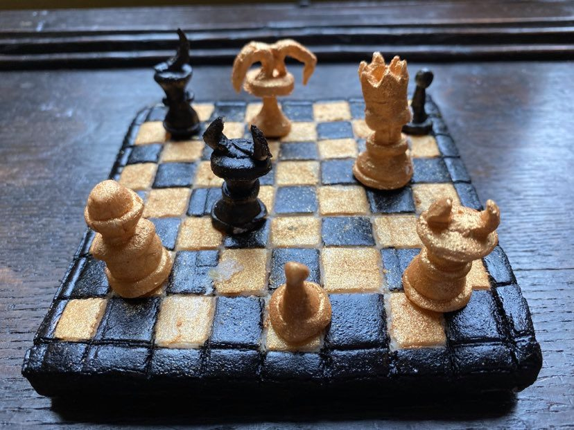 A chessboard made out of marchpane in black and gold