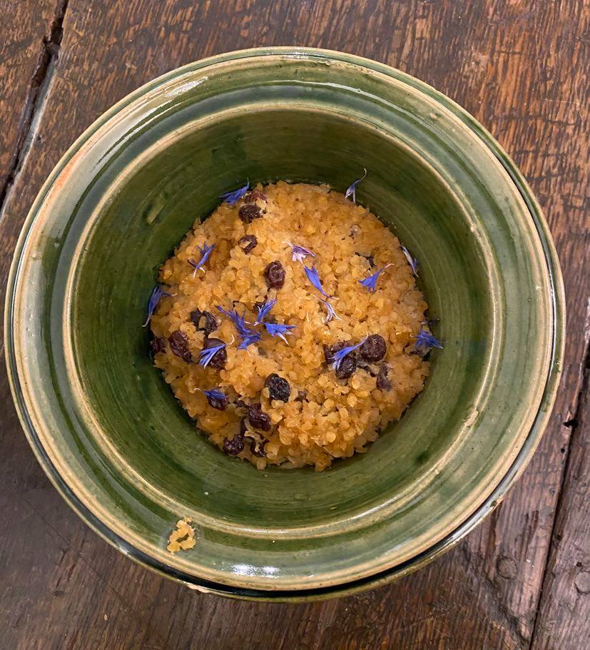 A bowl of Tudor food, baked wheat and currents decorated with small purple flowers